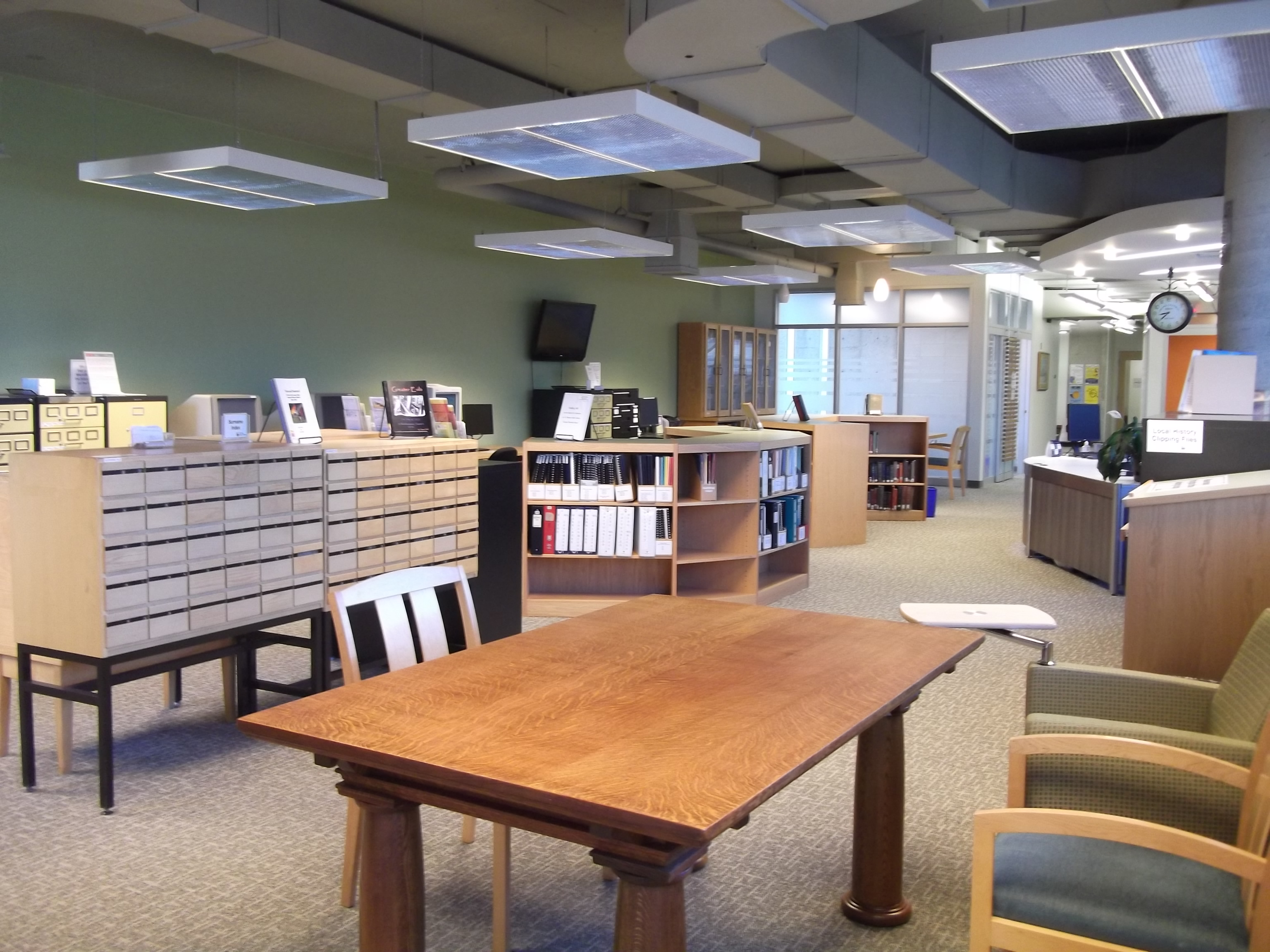 a large room with green walls, bookshelves, tables, chairs, and card catalogues