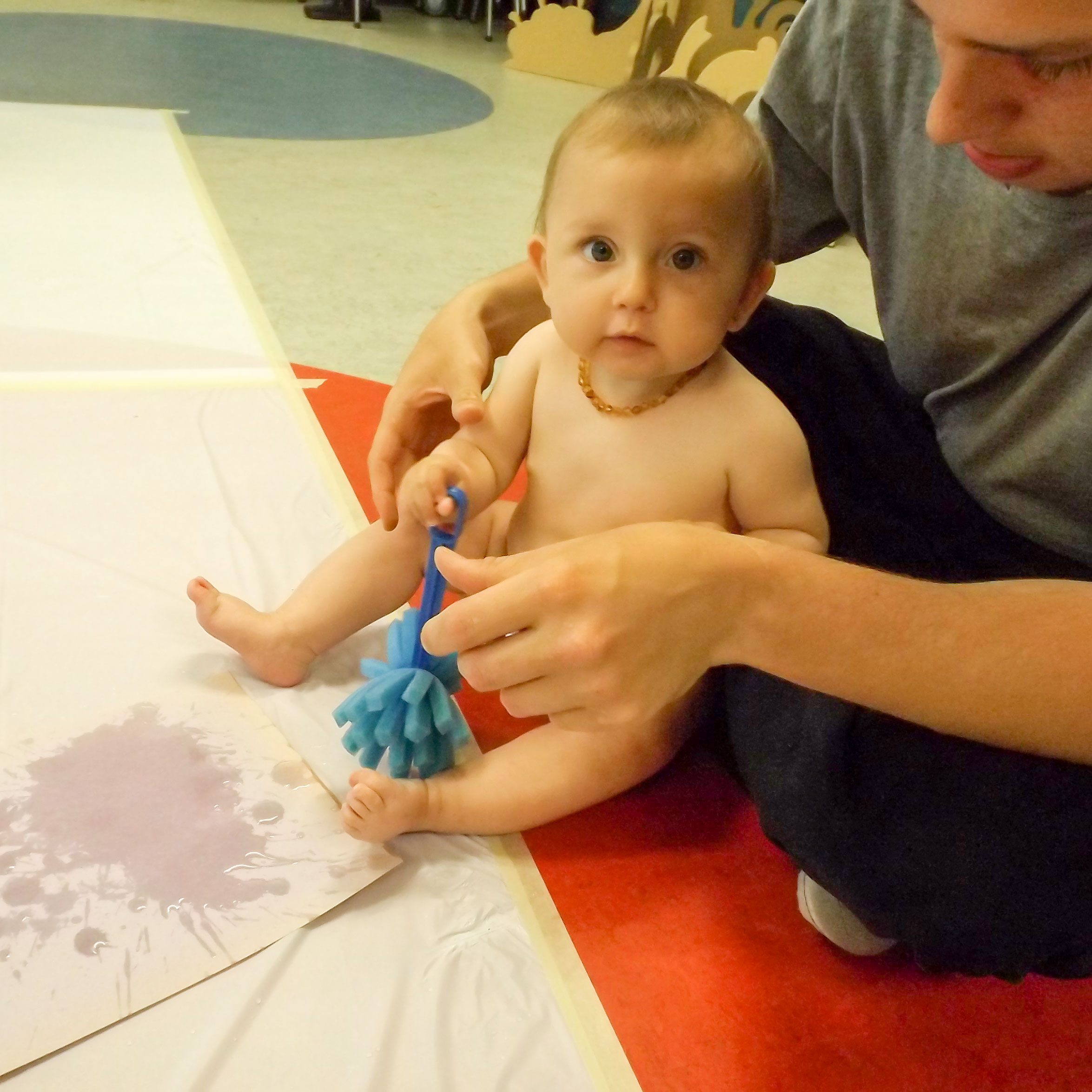 Parent with baby play with water and sponge on the colourful library floor. Baby is looking directly into the camera