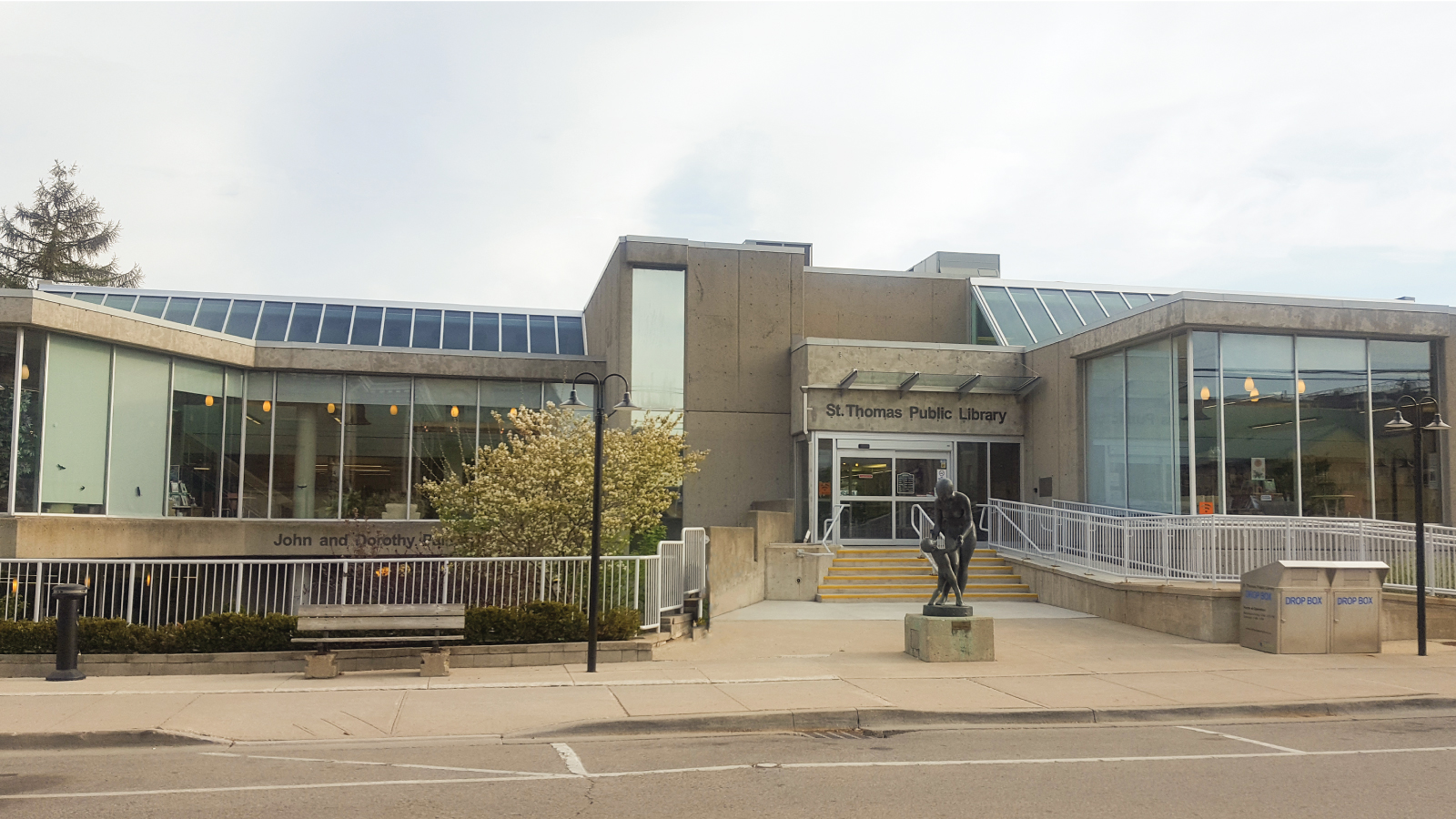 library building, a large grey concrete building with big windows, greenery, and a statue out front of a mother and child