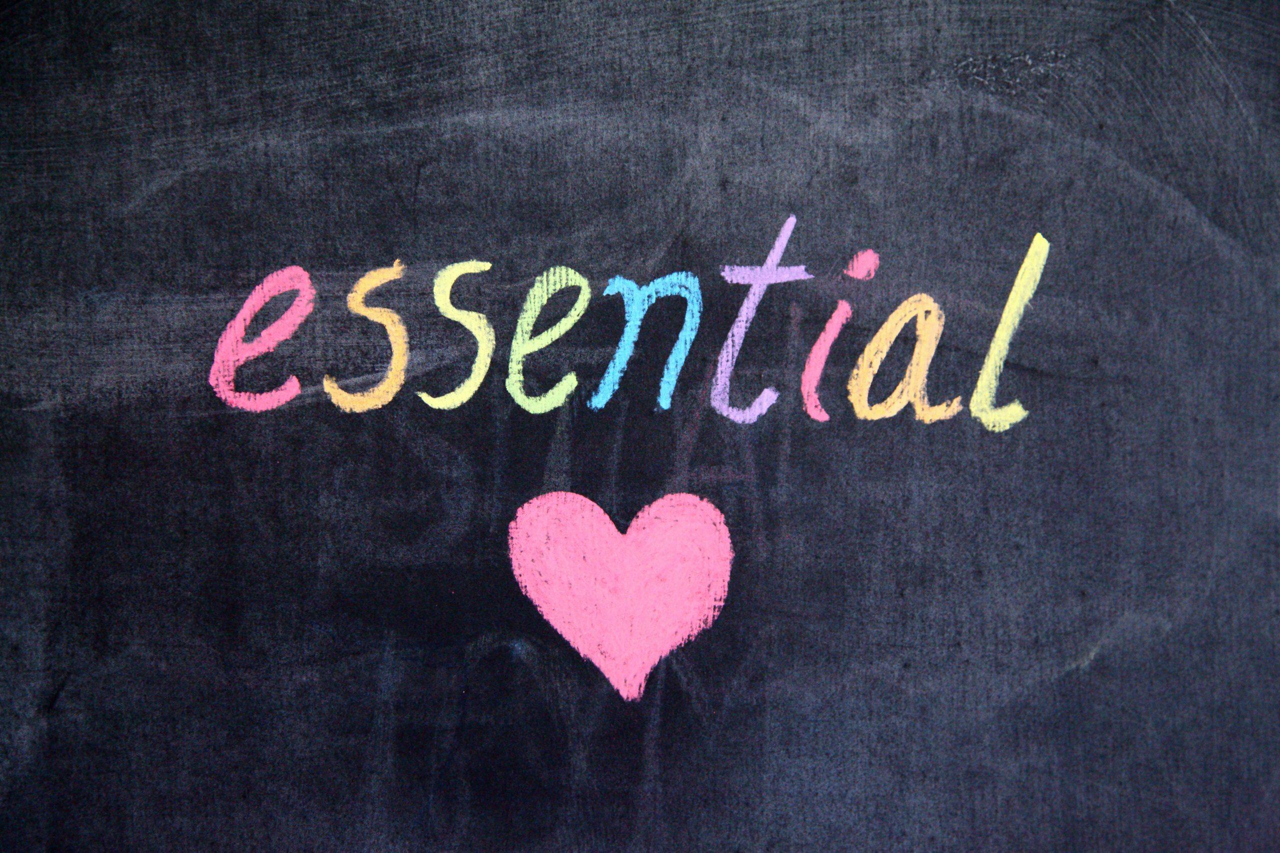 the work essential written in multicoloured chalk on black background