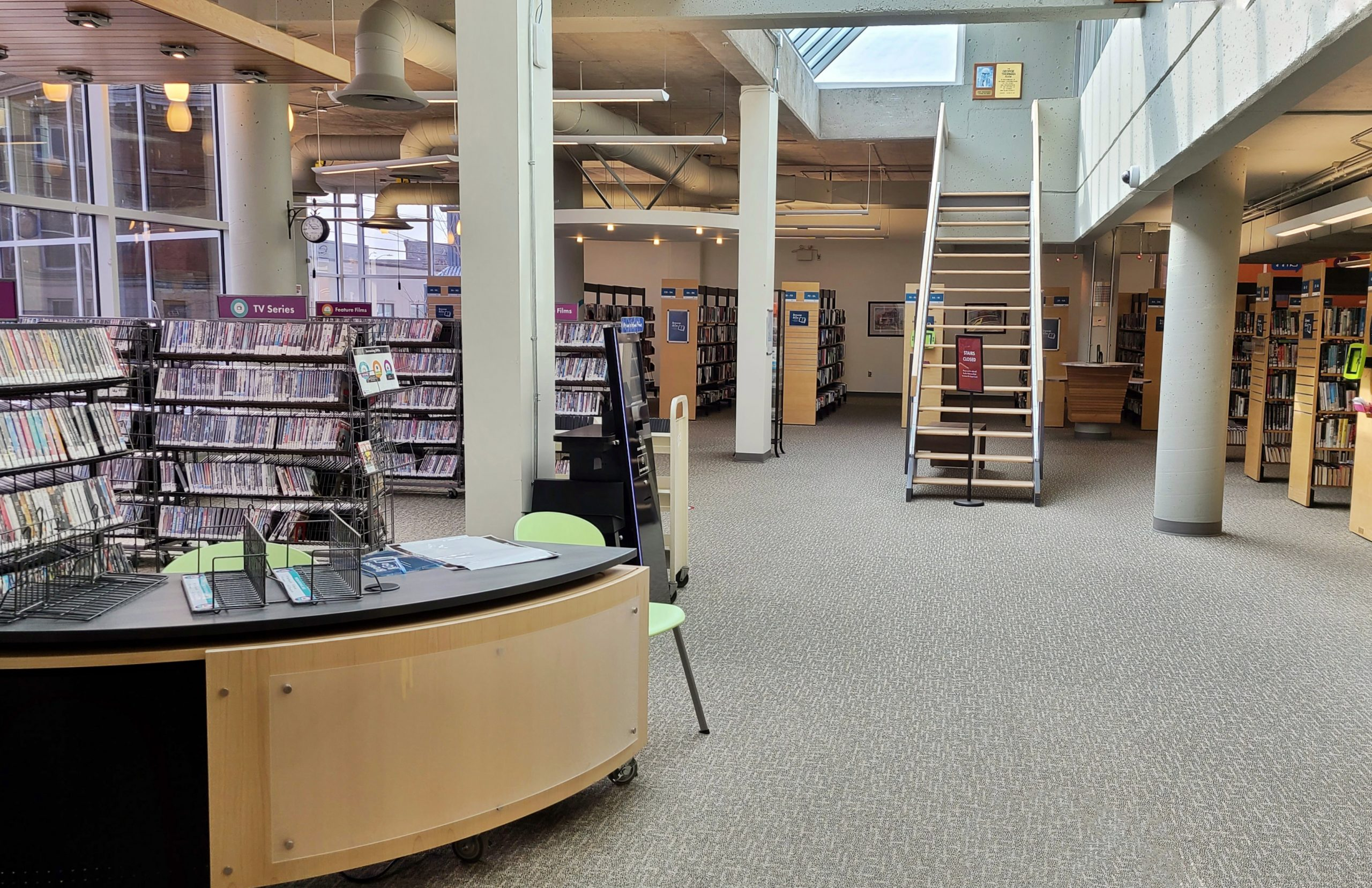 library service desk with bookshelves and rows of dvds behind it