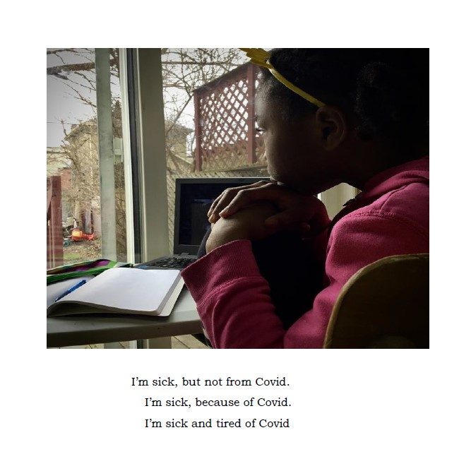 young girl sits in front of a laptop and schoolwork with her chin on her hands and hands on her knee looking out a window to a backyard area