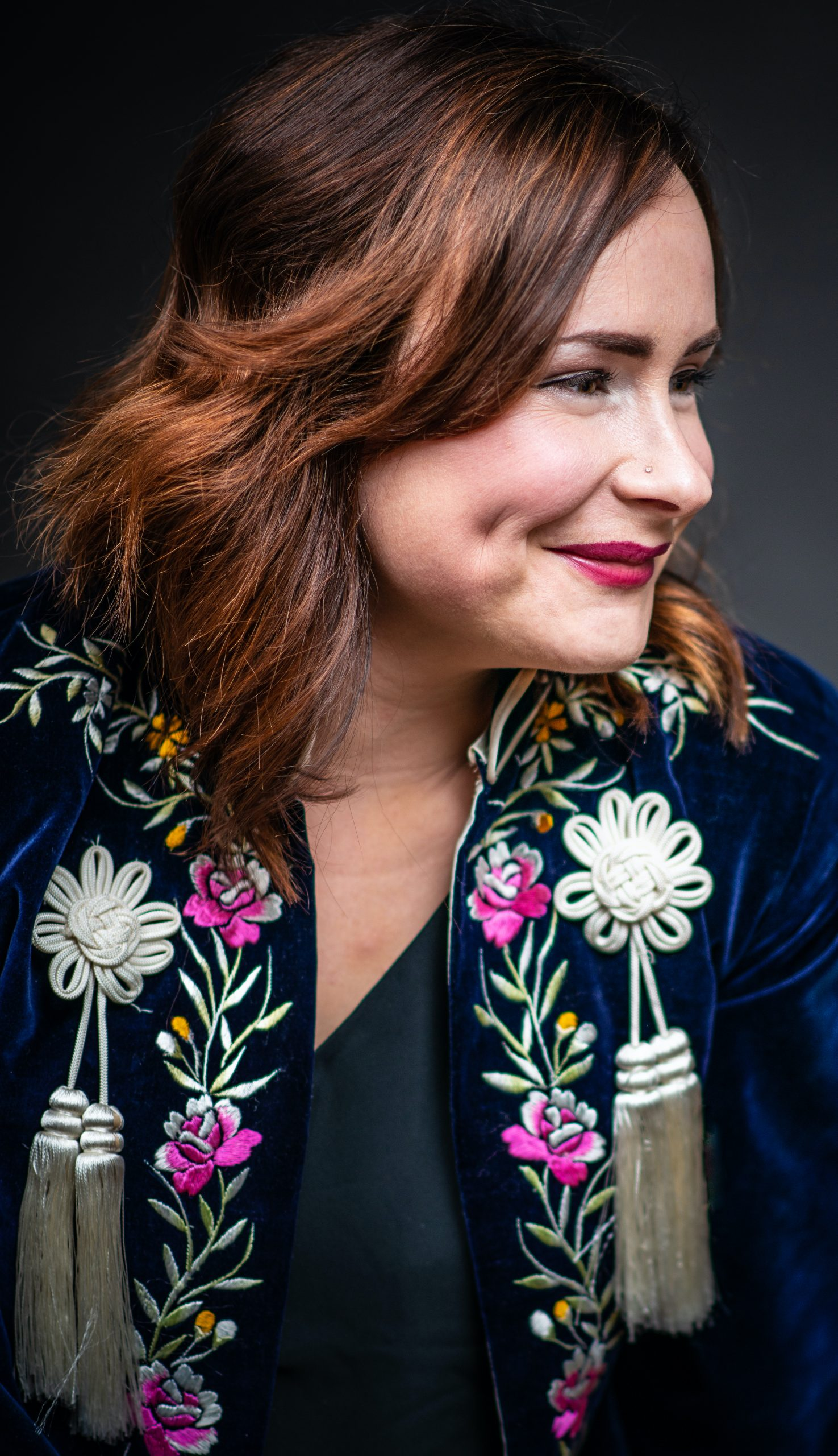image of writer in residence kayla geitzler. she has reddish hair with her face angled to the right. she wears red lipstick and a black jacket with pink, green, and white floral embroidery on it.
