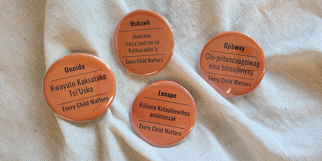 four orange buttons on canvas background. Each button has Every Child Matters written in either Mohawk, Ojibway, Lenape, or Oneida language