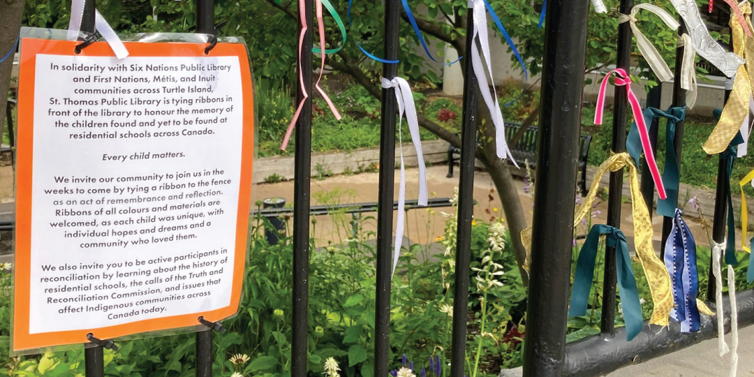 multicoloured ribbons hang on a black iron fence.
